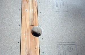 エアコン業者による柱と耐力面材への穴あけ。仕上げを撤去した写真。